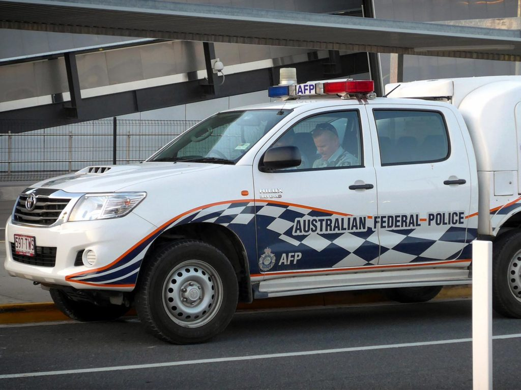 A picture of two police officers sitting in an Australian federal police car.