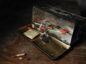 An open tin laying on its side on a wooden desk, revealing the drug paraphernalia inside and a single cigarette. The tin includes a syringes and a spoon.